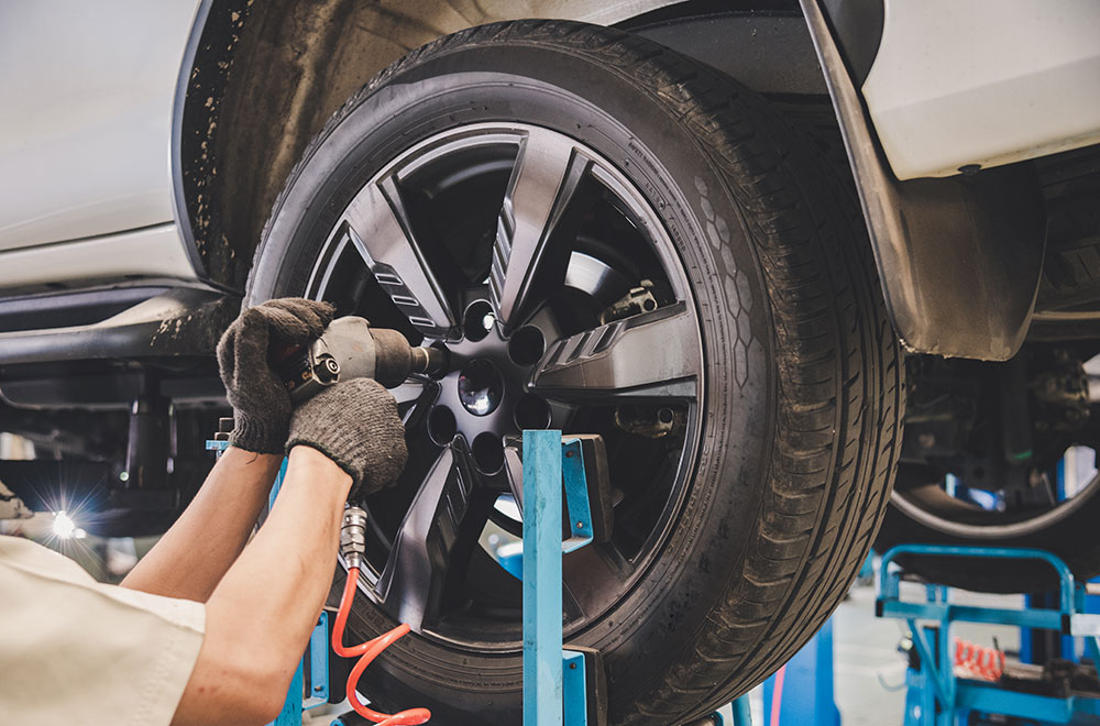 Mechanic changing a car tire in an auto shop