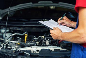 car maintenance and repair mechanic writing checklist paper on clipboard