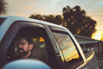 Bearded man in a truck going for a drive at dusk